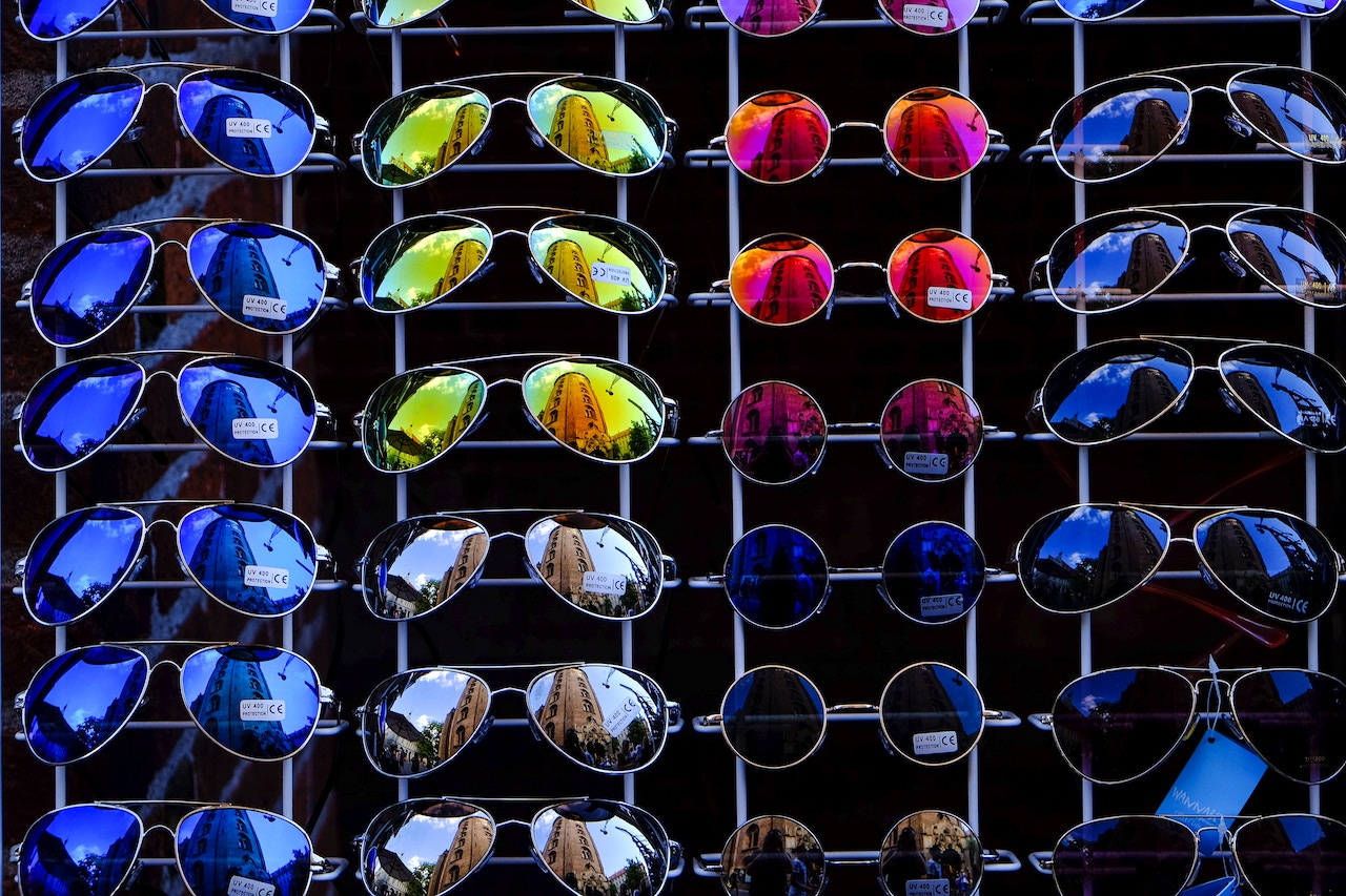 Assorted sizes and colors of sunglasses hanging on a wall