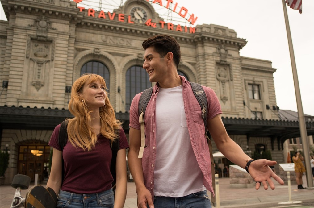 A girl and boy student walking together in front of Union Station downtown