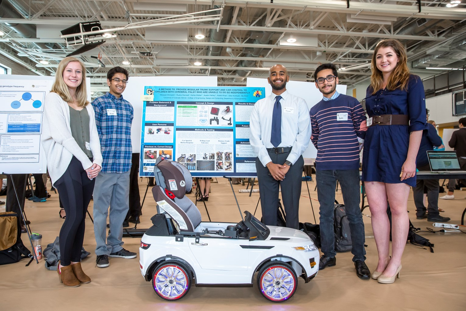 Engineering students at the College of Engineer, Design, and Computing final presentation forum, featuring a remote car as their project