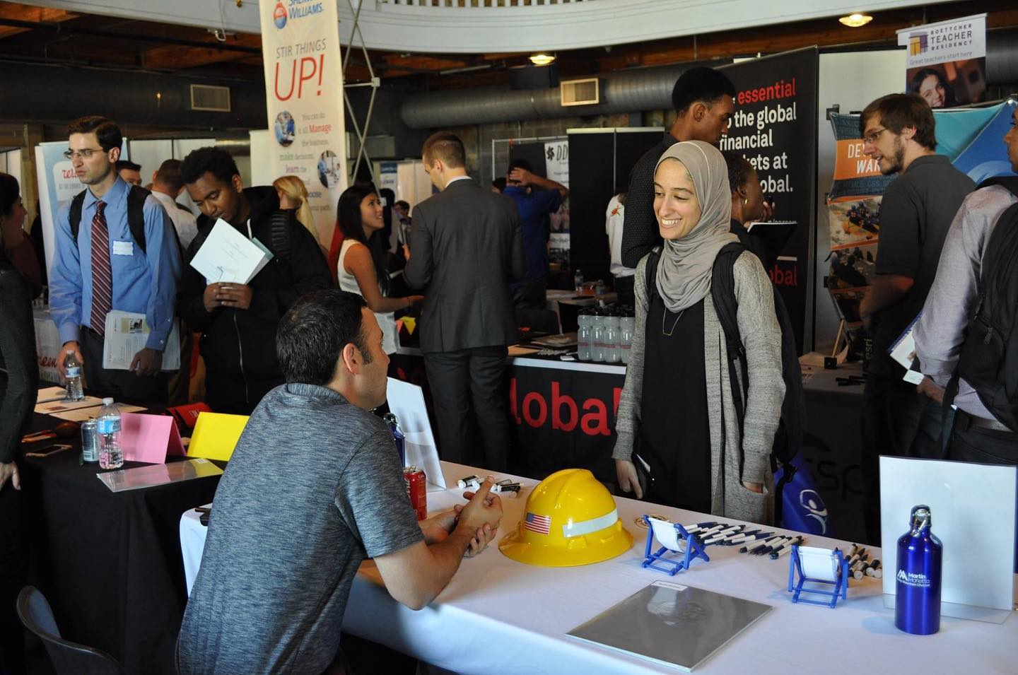 The College of Liberal Art and Science fair with one students chatting with a representative at a booth.