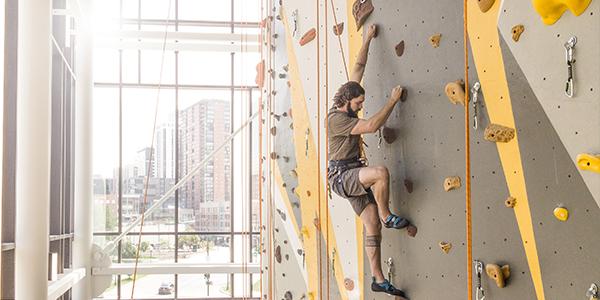Student traversing rock climbing wall