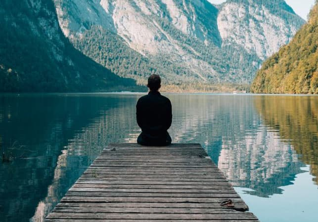 A person sitting by a placid lake