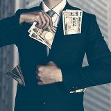 Business man stuffing money in jacket
