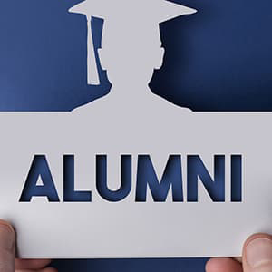 Silhouette of person wearing grad cap with the word alumni cut out below