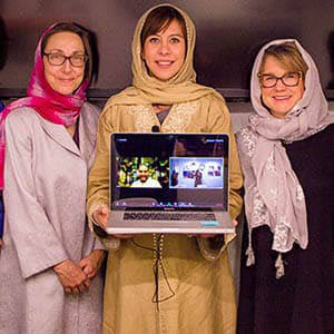 Alaa Al-Ban with two women hold a computer with her final project