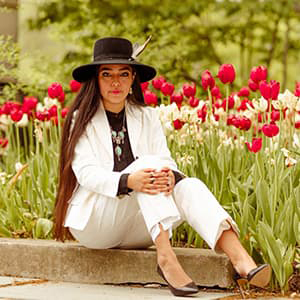 Anjelica Gallegos in a white pant suit sitting in front of a bed of tulips