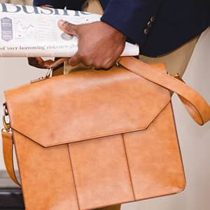 Person holding a briefcase and newspaper