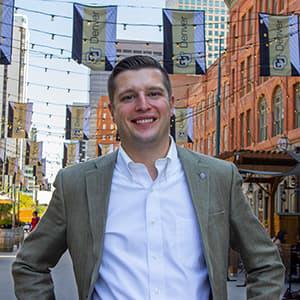 Regent Jack Kroll in Larimer Square with CU Denver flags hanging