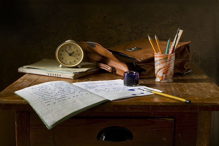 a collection of items including a notebook, pens, a clock and a bag rest on a wooden table