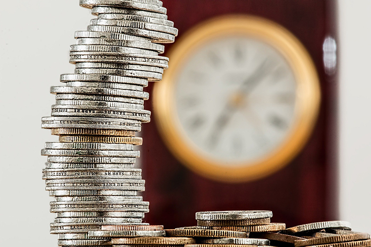 a stack of silver coins with a clock in the background