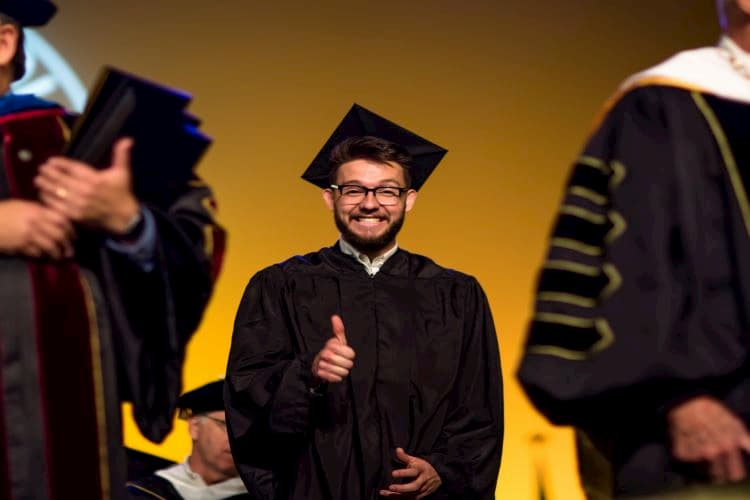 Male graduate smiling and giving a thumbs-up to the camera