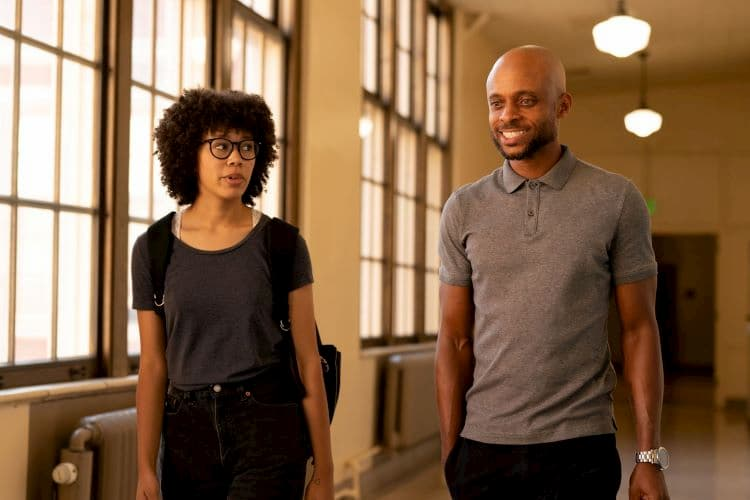 A man and woman walking down a hall and talking