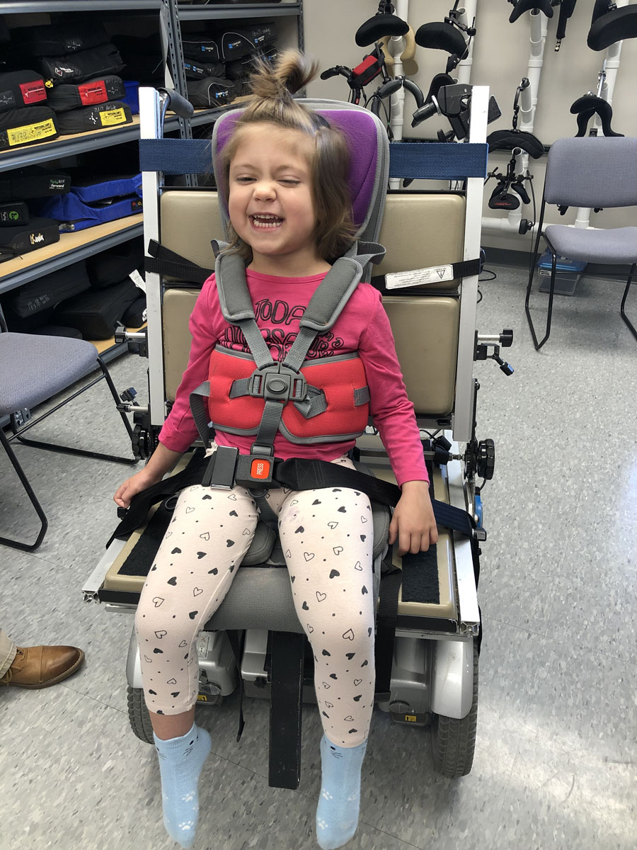 a young girl sits in a power wheelchair seating simulator